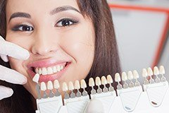 Closeup of woman's smile compared with tooth color chart