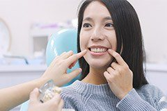 Woman in dental chair pointing to teeth